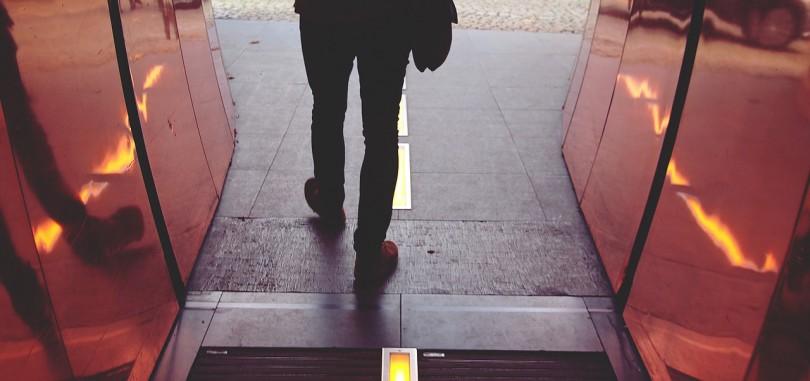 Photo of someone walking through an open door.